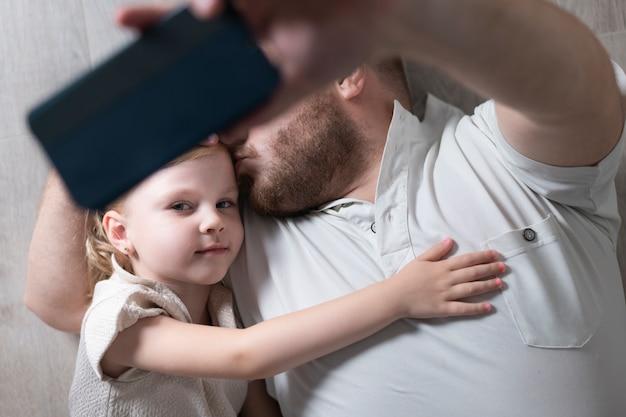 父は娘と一緒にselfieを取る 無料写真