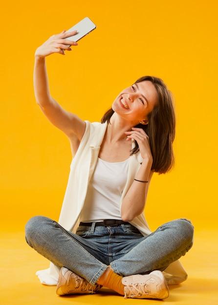 Selfieを取る女性の正面図 無料写真