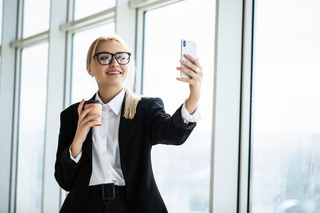 正式な摩耗立っているテイクアウトコーヒーを手で押し、オフィスで携帯電話でselfieを取って秘書の女性の写真 無料写真