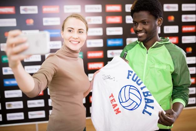 サッカー選手がファンと一緒にselfieを取る Premium写真
