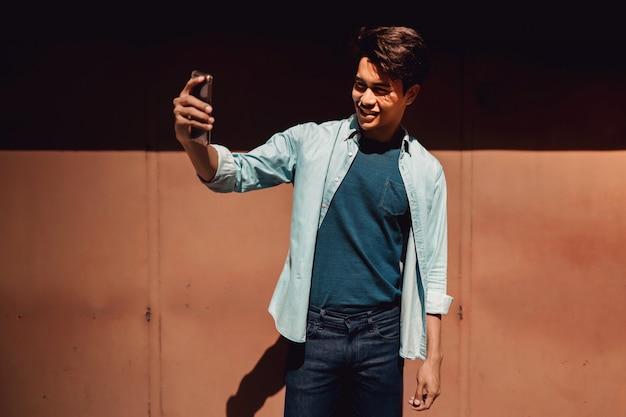 Selfieを取るに携帯電話を使用しながら笑って幸せな若い男の肖像画。 Premium写真