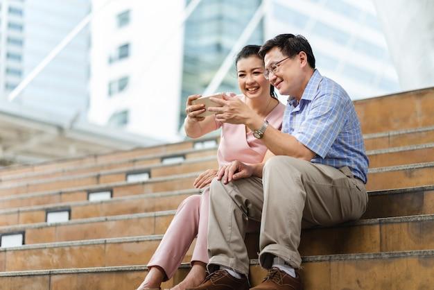 市内の階段に座ってスマートフォンと一緒に幸せなアジアカップルシニア観光客selfie写真 Premium写真