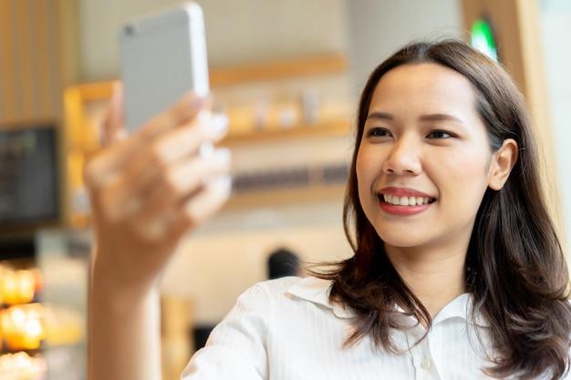 スマートフォンを保持し、selfieスナップショットまたはライブビデオのフロントカメラを使用してアジアの美しい女性 Premium写真