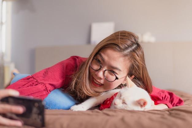 アジアの女性がベッドの上のselfieのためにスマートフォンを使用して Premium写真