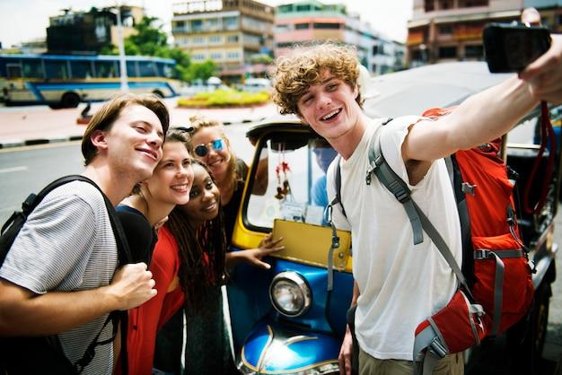 トゥクトゥクの前でselfieを取っている白人観光客のグループ Premium写真