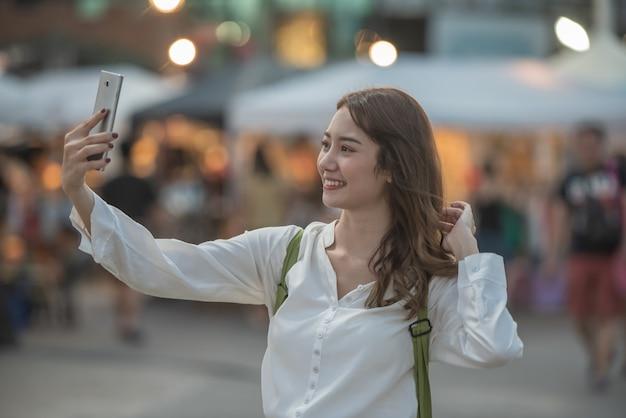 ショッピングナイトマーケットで彼女のスマートフォンでselfieを取って若い幸せな女。 Premium写真