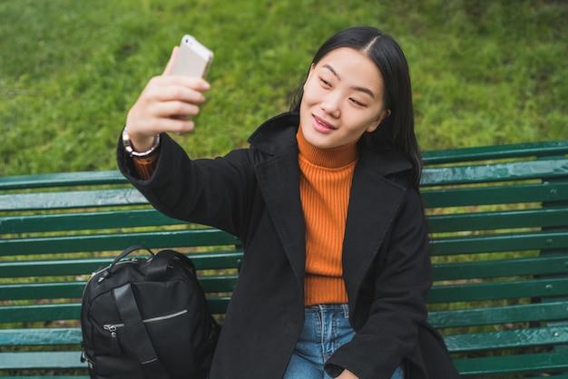 電話でselfieを取ってアジアの女性。 無料写真