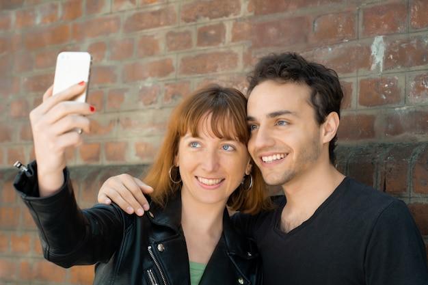 Молодая пара принимая selfie с мобильного телефона на открытом воздухе. Premium Фотографии