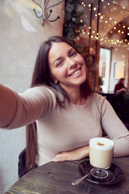 Красивая счастливая девушка принимая selfie в кафе во время рождественских праздников Premium Фотографии