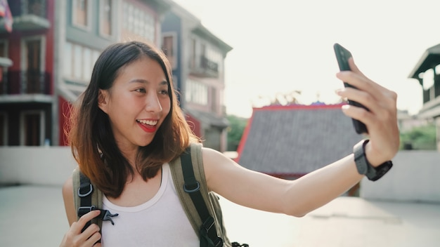 Selfieを取ってスマートフォンを使用して陽気な美しい若いアジアのバックパッカーブロガー女性 無料写真