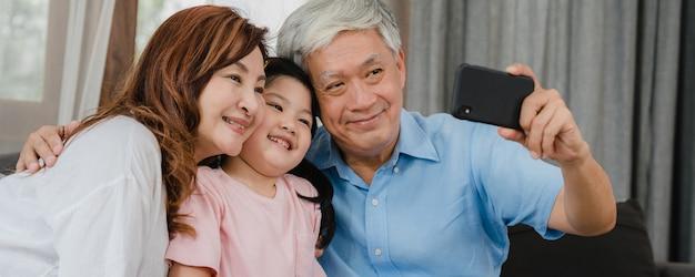 自宅で孫娘とアジアの祖父母selfie。シニア中国の幸せな家族の時間を過ごすには、リビングルームのソファーに横になっている若い女の子の子供と携帯電話を使用してリラックスします。 無料写真