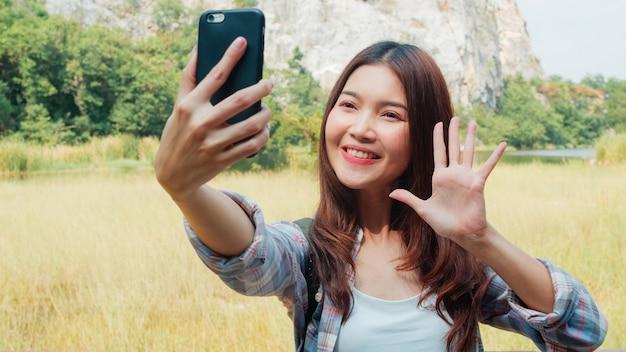 山の湖でバックパックのselfieと陽気な若い旅行者アジアの女性。自分撮りを取って携帯電話を使用して幸せな韓国の女の子は、ハイキングの冒険で休日をお楽しみください。ライフスタイル旅行し、コンセプトをリラックスします。 無料写真