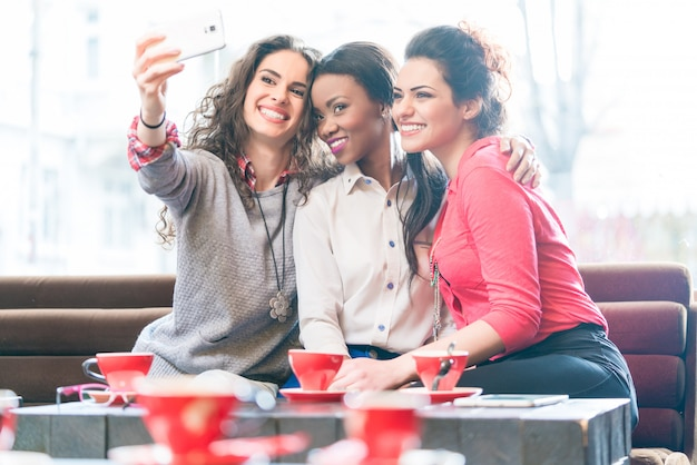Selfieを取ってカフェの若い女性 Premium写真