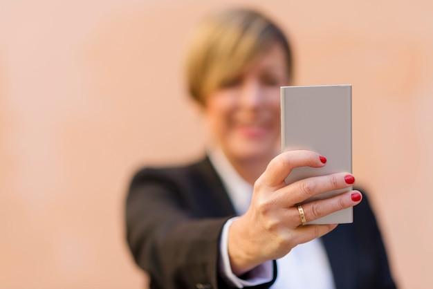 彼女のスマートフォンとselfieの肖像画を取って熟女 Premium写真