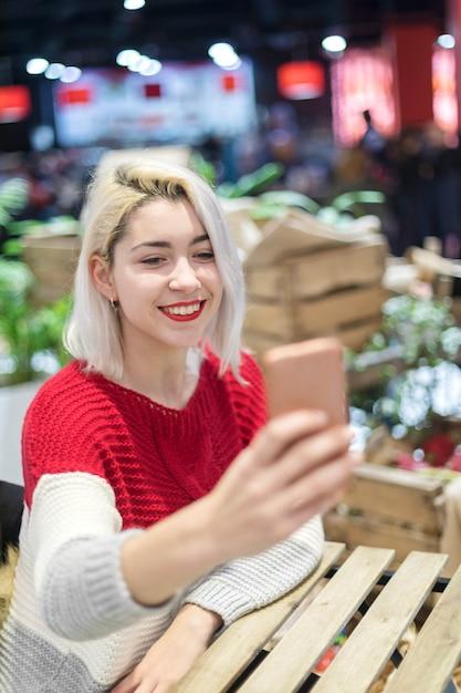 バーでselfieを取っている若い美しい女性の側面図です。 Premium写真