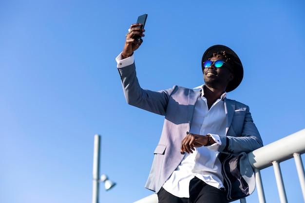 帽子とサングラス、selfieをしながらリラックスした金属フェンスに寄りかかって身に着けている若いアフリカ黒人男性の低角度のビュー Premium写真