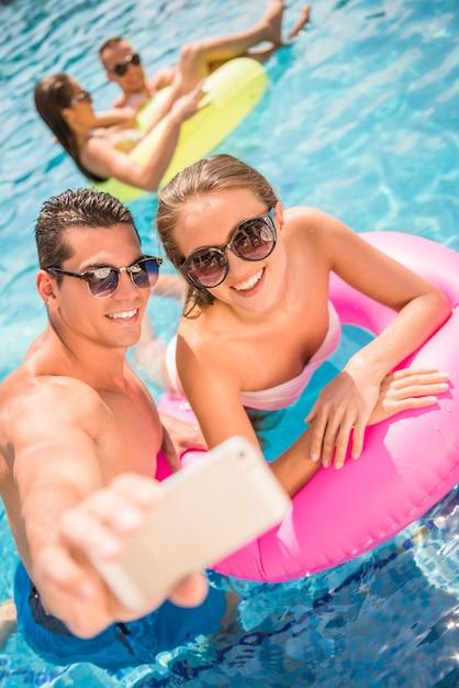 幸せなカップルはプールで楽しんでいる間selfieを作っています。 Premium写真