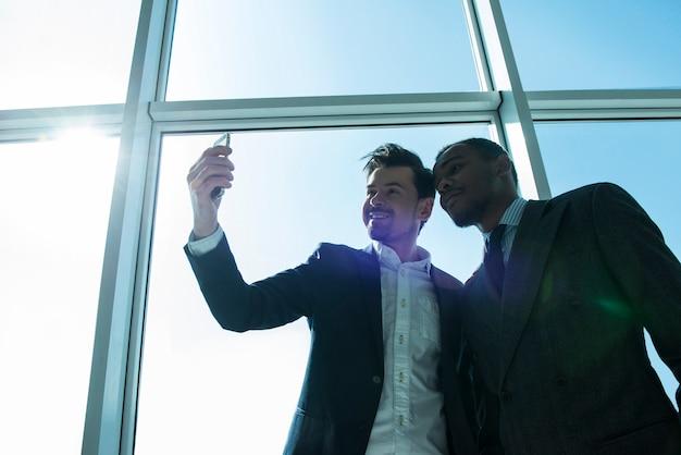 ビジネスマンは、近代的なオフィスでselfie写真を作っています。 Premium写真
