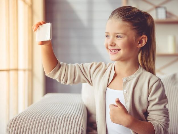 カジュアルな服でかわいい女の子がselfieをやっています。 Premium写真