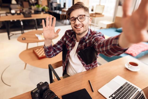 Фрилансер человек принимает selfie на ноутбуке, сидя за столом. Premium Фотографии