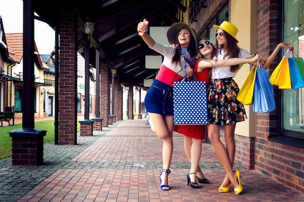 ショッピングの後、selfieを行うショッピングバッグとカラフルなドレス、帽子、ハイヒールでかなり幸せな明るい女性女性の女の子の友人 Premium写真