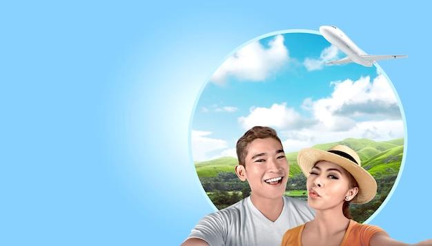 緑の丘の背景を持つselfieを取って帽子とアジアカップル Premium写真