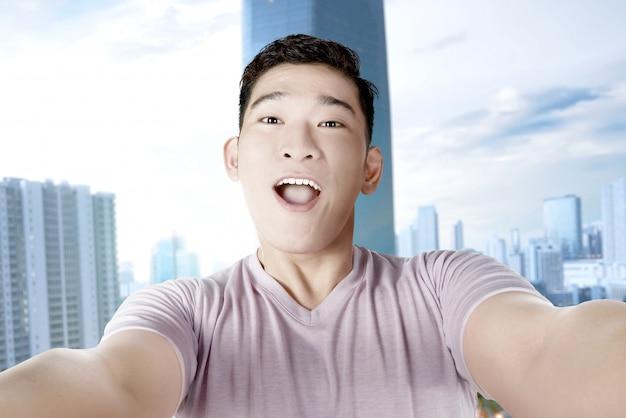 彼のスマートフォンでselfieを作るアジア人 Premium写真
