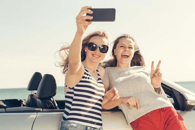 幸せな友達が車でselfieを引き継ぐ Premium写真