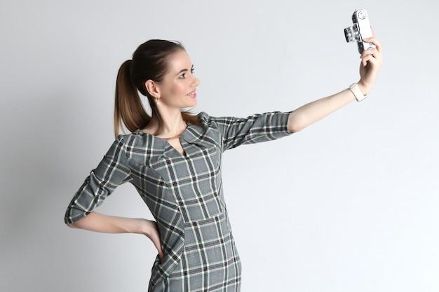 若い女性は、上からビンテージカメラの助けを借りてselfieを取る Premium写真