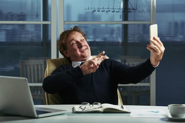 彼のオフィスの机でselfiesを取って中年の男 無料写真