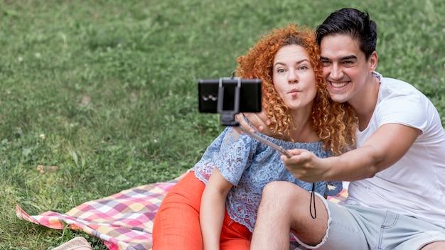 若いカップル、selfiesを取ってピクニック中に楽しんで 無料写真