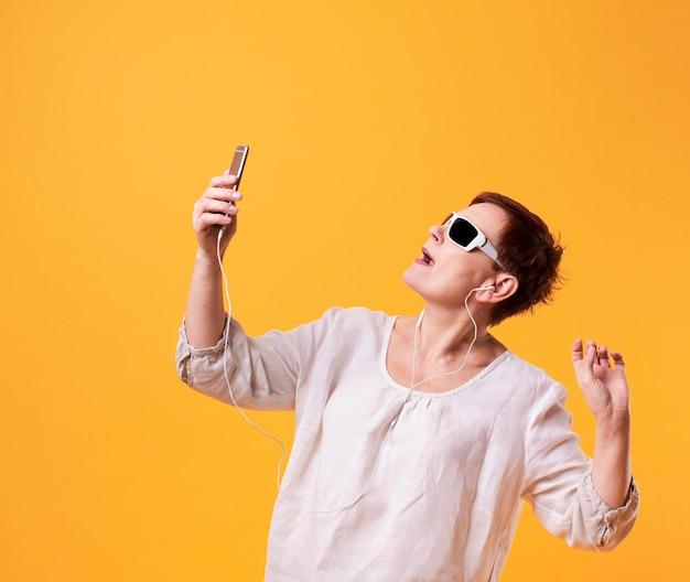 黄色の背景にselfiesを取って年配の女性 無料写真