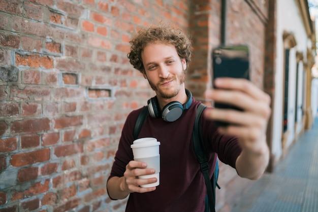 電話でselfiesを取る若い男。 Premium写真
