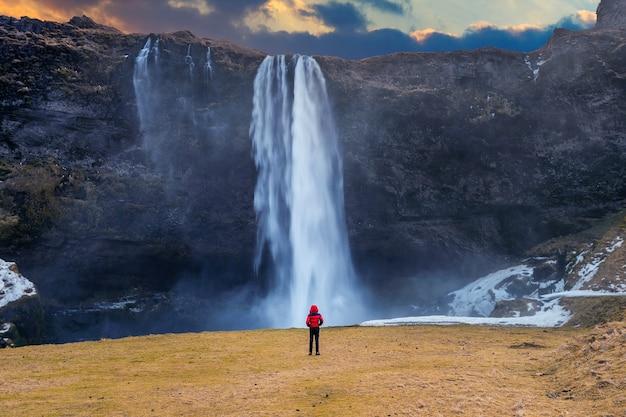 アイスランドのセリャラントスフォスの滝。赤いジャケットを着た男がセリャラントスフォスの滝を見ています。 無料写真