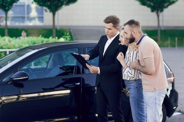 Продавец и молодая пара на природе возле новой машины. продавец рассказывает молодой паре о машине. мужчина и женщина покупают машину. Premium Фотографии