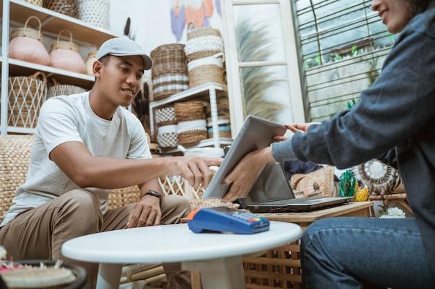 Продавец и покупатель используют таблицы и устройства электронного сбора данных в качестве средства оплаты в ремесленной мастерской. Premium Фотографии
