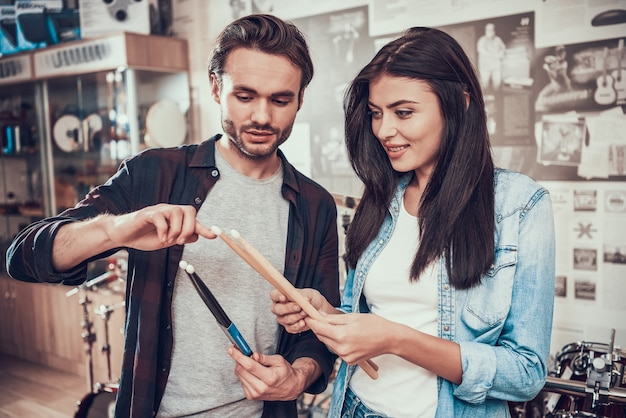 Seller demonstrates drumsticks to pretty girl in music store Premium Photo