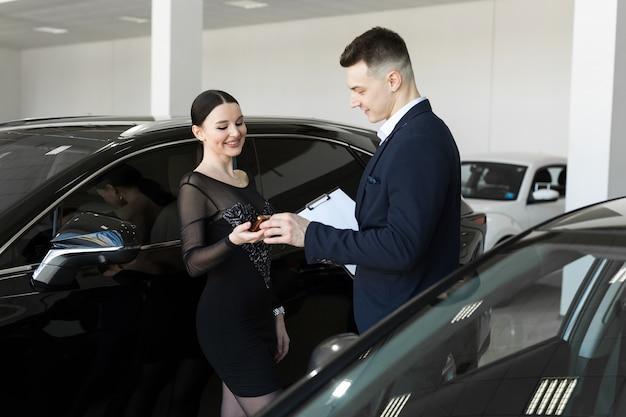 Продавец передает покупателю ключи от новой машины в автосалоне. Premium Фотографии
