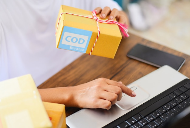 Selling online ecommerce shipping online shopping delivery and order startup small business owner working concept - woman packing cardboard box parcel delivery to customer cash on delivery express Premium Photo