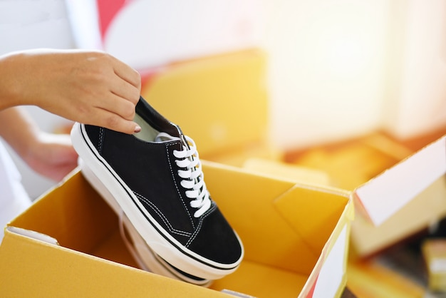 Selling online shopping - woman packing shoes sneakers in cardboard box prepare parcel box to delivery service customer ecommerce delivery shopping online and order concept Premium Photo