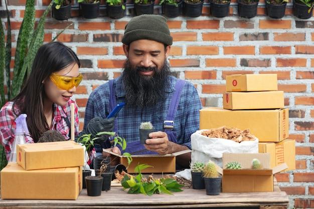 온라인으로 식물 판매 휴대 전화로 사진 식물을 찍는 동안 행복한 커플 무료 사진