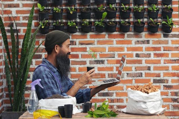 植物をオンラインで販売する;植物とラップトップのポットを持っている男 無料写真