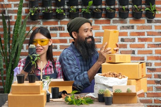 植物をオンラインで販売する;販売者は笑顔で植物のポットと配送ボックスを手に持っています 無料写真