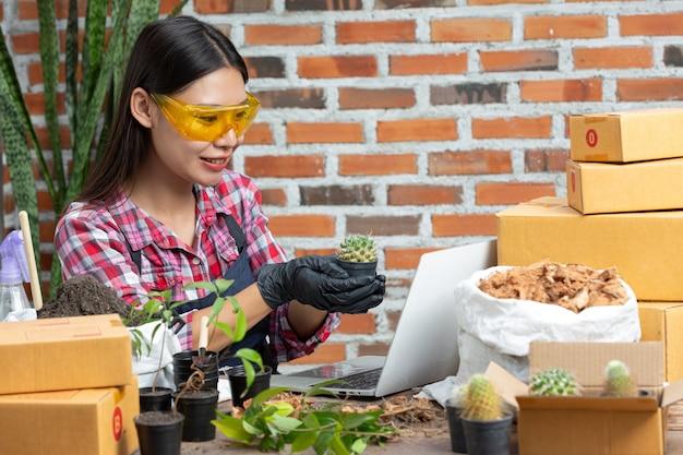 Vendita di piante online; donna che tiene un vaso di pianta e collegamento con il cliente sul computer portatile Foto Gratuite