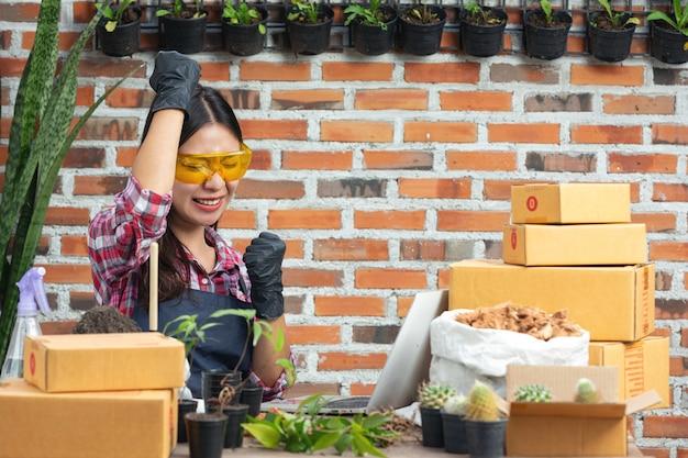 植物をオンラインで販売する。ノートパソコンを使用しながら喜んでいる女性 無料写真