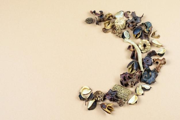 ベージュパステル紙の背景に乾燥バニラの花と葉のセミリース。 Premium写真