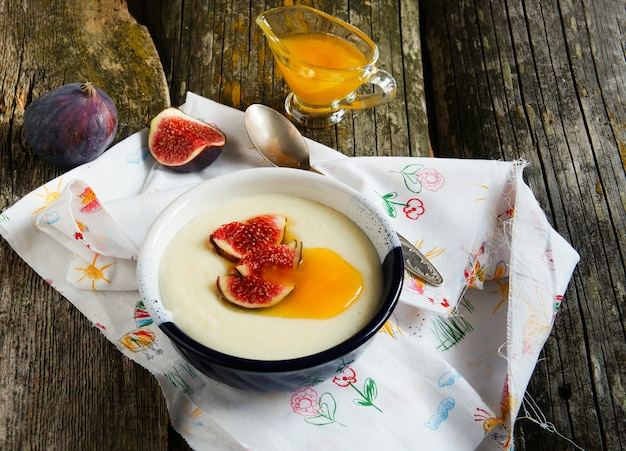 Semolina porridge with figs and honey o the old wooden bakground Premium Photo