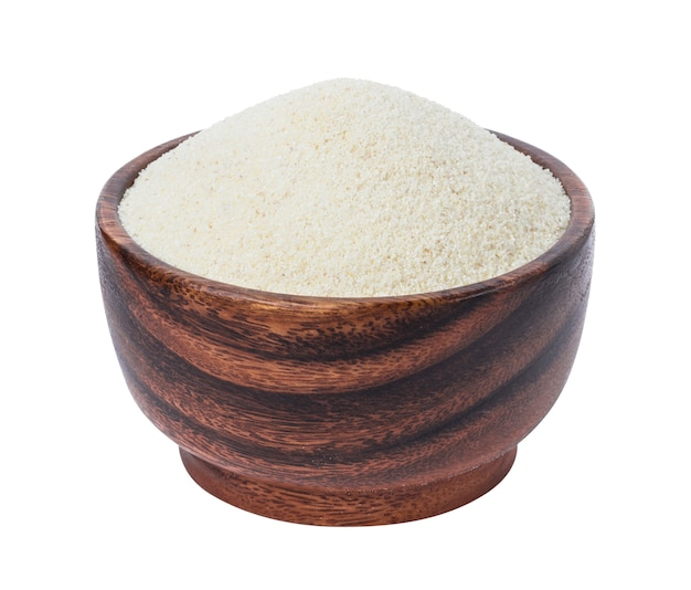 Semolina in wooden bowl isolated on white Premium Photo