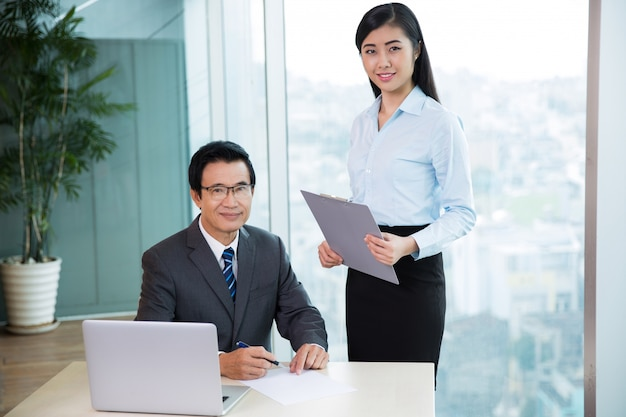 Senior asian boss signing document and secretary Free Photo