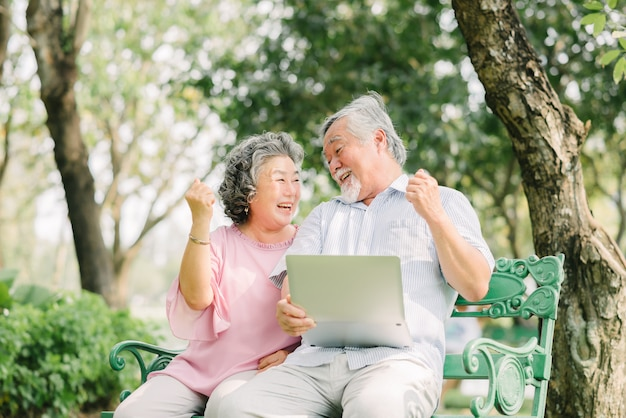 Senior asian couple laughing with laptop in park Premium Photo